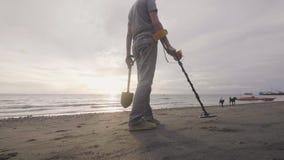 耳机的人工作在海滩的扫描的沙子与金属探测器发现贵重物品的在日落 股票视频