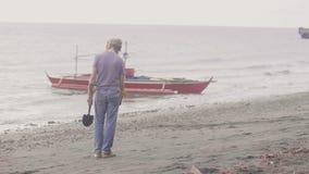 耳机的人是在海滩藏品探测器的workingg发现在沙子的贵重物品在海岸线在日出 股票视频