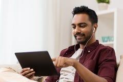耳机的人有片剂个人计算机的听到音乐的 库存图片