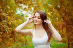 耳机的十几岁的女孩在自然 免版税库存照片