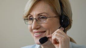 耳机的友好的微笑的老妇人讲话与客户,电话中心支持 影视素材