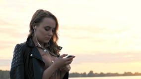 耳机的可爱的女孩使用在自然的智能手机走,听到音乐和浏览在智能手机的 股票录像