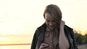 耳机的可爱的女孩使用在自然的智能手机,听到音乐和浏览在智能手机 股票录像