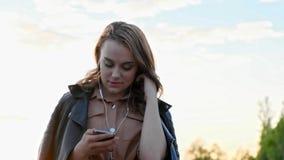 耳机的可爱的女孩使用智能手机,听到音乐和浏览在智能手机 影视素材