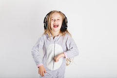 耳机的可爱的小女孩享用与音乐 免版税库存图片