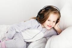 耳机的可爱的小女孩享用与音乐 库存照片