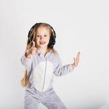 耳机的可爱的小女孩享用与音乐 免版税库存照片