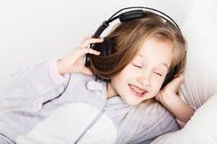 耳机的可爱的小女孩享用与音乐 免版税图库摄影