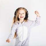 耳机的可爱的小女孩享用与音乐 库存图片