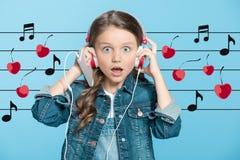 耳机的可爱的小女孩 免版税库存图片