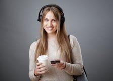 耳机的可爱的年轻微笑的女孩拿着一个电话和一杯咖啡 免版税库存图片