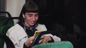耳机的听到音乐和浏览在公共交通工具的手机的年轻时髦的妇女画象  ?? 股票录像