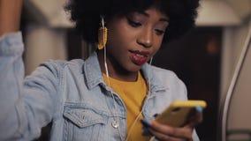 耳机的听到音乐和浏览在手机的年轻非裔美国人的妇女画象公开 影视素材