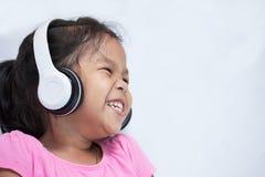 耳机的听逗人喜爱的亚裔儿童的女孩音乐 免版税库存照片