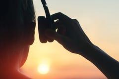耳机的女孩听到音乐的在城市在日落 免版税库存照片