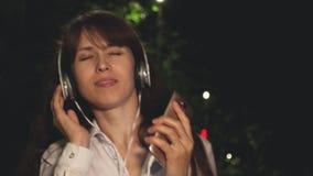耳机的女孩和接触在晚上给挥动的长头发从音乐的唱歌的和跳舞的微笑和kayfuya打电话在公园 股票录像