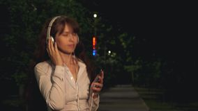 耳机的女孩和接触在晚上给挥动的长的头发和跳舞的微笑和得到蜂声打电话从音乐在公园 股票视频