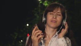 耳机的女孩和接触在晚上给挥动的长的头发和跳舞的微笑和得到蜂声打电话从音乐在公园 影视素材