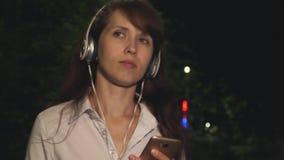 耳机的女孩在晚上包括从音乐的电话挥动她长的头发和跳舞微笑的歌曲有联系和kayfuya 股票录像