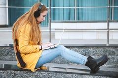 耳机的女孩拿着一台膝上型计算机,坐大学的步 库存图片