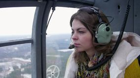 耳机的女孩有话筒位子飞行直升机的 噪声 运输 在地面上 股票录像
