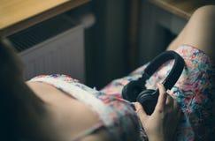 耳机的女孩由窗口 免版税库存图片