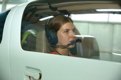 耳机的女孩飞行员在体育平面准备好飞行 免版税图库摄影