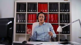耳机的女实业家在商业中心的跳舞和唱一首歌曲 影视素材