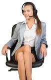 耳机的女实业家坐办公室椅子 免版税库存照片
