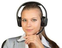 耳机的女实业家坐椅子,手 库存图片
