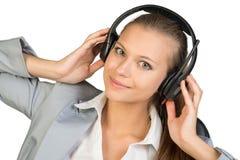 耳机的女实业家用她的手 免版税库存照片