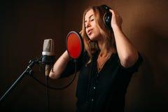 耳机的女歌手反对话筒 库存照片