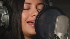 耳机的女歌手反对话筒 免版税库存图片