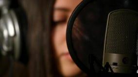 耳机的女歌手反对话筒 库存图片