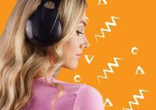 耳机的妇女反对与白色样式的橙色背景 图库摄影