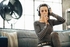 耳机的妇女唱歌入在顶楼公寓的一个话筒的 免版税库存照片