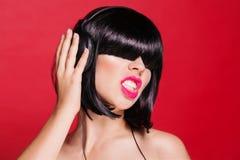 耳机的妇女DJ享受舞蹈的 在红色 免版税图库摄影