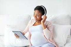 耳机的孕妇有片剂个人计算机的 免版税库存图片