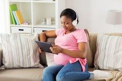 耳机的孕妇有片剂个人计算机的 库存照片