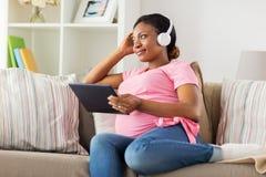 耳机的孕妇有片剂个人计算机的 免版税库存照片