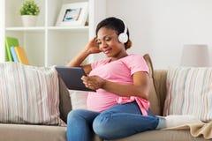 耳机的孕妇有片剂个人计算机的 图库摄影