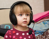 耳机的小白肤金发的女孩 免版税库存照片