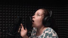 耳机的少女排练在音乐声音演播室的 可爱的妇女录音歌 股票录像