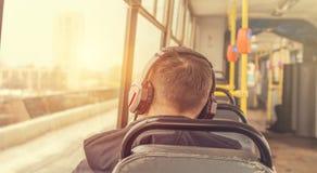 耳机的年轻人在电车 免版税库存照片