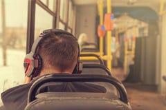 耳机的年轻人在电车 免版税库存图片