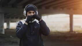 耳机的年轻人拳击手训练拳打的在都市地点户外在冬天 库存照片