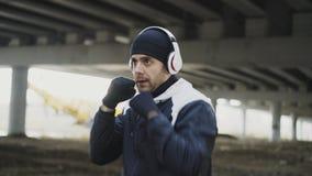 耳机的年轻人拳击手训练拳打的在都市地点户外在冬天 免版税库存照片
