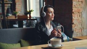 耳机的年轻女人听到音乐的使用在现代咖啡馆的智能手机 股票录像