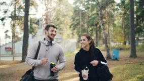耳机的年轻帅哥与他女性朋友和笑的以后走谈话在有体育袋子的公园 股票视频