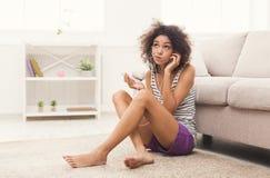 耳机的年轻怀疑妇女在地板上 库存照片